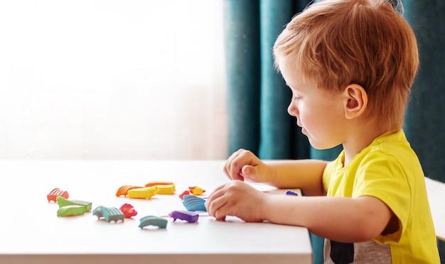 Blanke babyblonde beeldhouwen uit kinderdeeg voor thuis beeldhouwen aan tafel, kinderen en creativiteit, de ontwikkeling van fijne motoriek