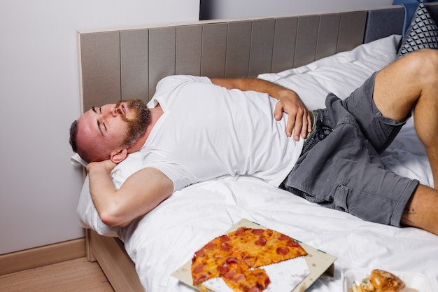 Blanke bebaarde man ligt op slecht na overmatige fastfoodpizza en hamburgers