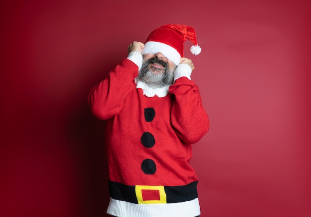 Blanke bebaarde man met de kerstman is een te grote hoed voor hem