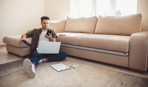 Blanke bebaarde man met een telefoon ligt op de vloer met behulp van een laptop terwijl hij op afstand online werkt