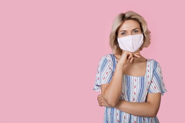 Blanke blonde vrouw die een medisch masker draagt, poseert in een jurk op een plukmuur die reclame maakt voor iets