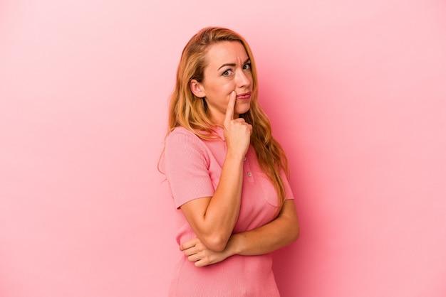 Blanke blonde vrouw geïsoleerd op roze achtergrond ongelukkig in de camera kijken met sarcastische uitdrukking.