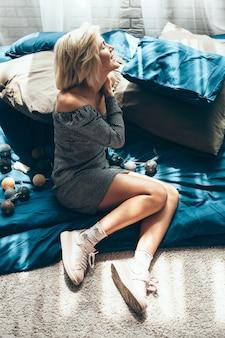 Blanke blonde vrouw ligt op de vloer op een deken in de buurt van nieuwjaarsversieringen glimlachend op een zonnige dag