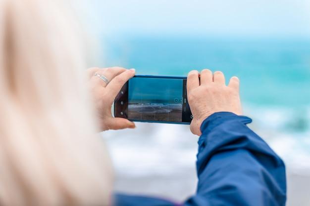 Blanke blonde vrouw maakt foto's of neemt video op smartphone op het strand in de buurt van de oceaan, vakantieconcept