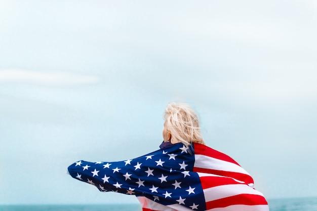 Blanke blonde vrouw met amerikaanse vlag die tegen de rug leunt en naar zee kijkt. amerikaanse vlag voor onafhankelijkheidsdag