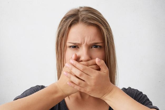 Blanke blonde vrouw met boze blik fronsen haar wenkbrauwen die mond bedekken met handen die proberen de tong vast te houden. stijlvolle vrouw die stilte probeert te houden en geen geheim vertelt
