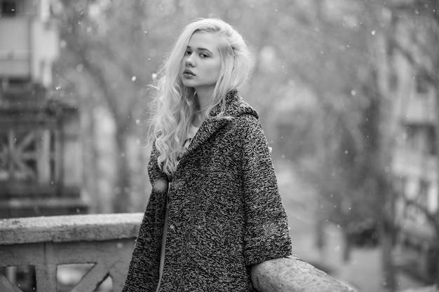 Blanke blonde vrouw met krullend haar, alleen zittend op een balkon. winterseizoen. zwart-wit beeld.