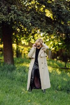 Blanke blonde vrouw wearind geul glimlach gelukkig op zonnige lentedag buiten wandelen in het park