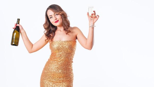 Blanke brunette vrouw in een gouden jurk drinkt champagne, plezier op een feestje op een witte achtergrond