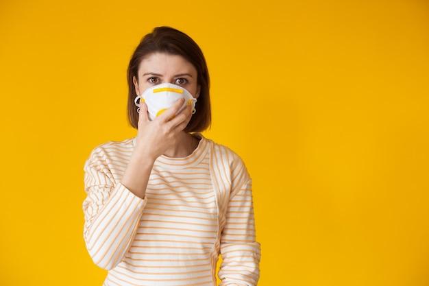 Blanke dame die zich voordeed op een gele achtergrond met vrije ruimte terwijl ze een masker met filter draagt