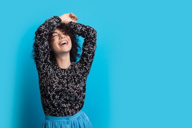 Blanke dame met krullend haar poseren met handen omhoog en glimlach in een blauwe jurk op een muur met vrije ruimte