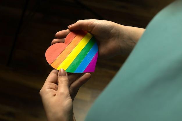 Blanke dame met regenboogkleur vlag in hartvorm, symbool van lgbt pride maand vieren, gemeenschap van homo's, lesbiennes, biseksuelen en transgenders, mensenrechten concept foto