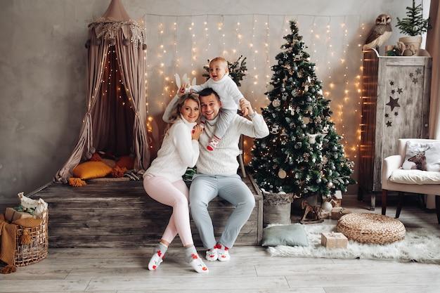 Blanke familie speelt thuis met hun jonge kind in een woonkamer met een kerstboom