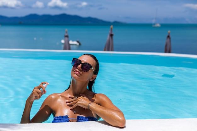 Blanke gebruinde vrouw glanzende bronzen huid bij zwembad in blauwe bikini op zonnige dag