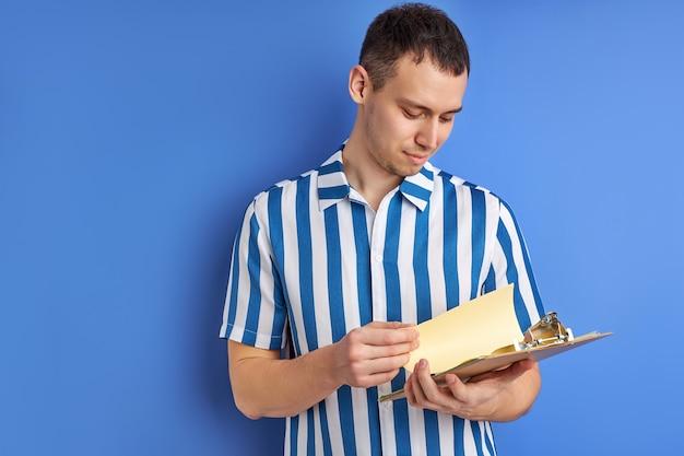 Blanke geconcentreerde man poseren met klembord met papieren document het lezen van notities