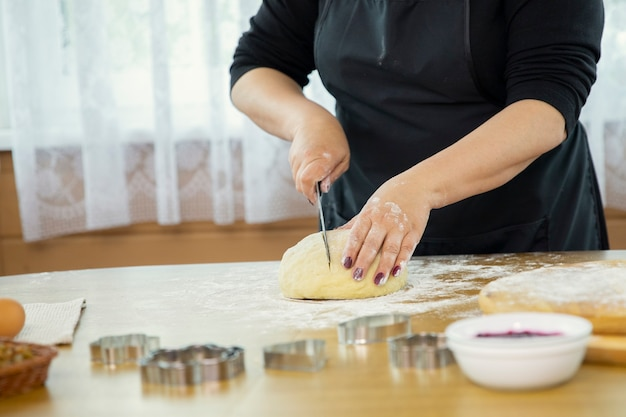 Blanke huisvrouw snijdt een stuk rauw deeg af met een mes om een dessert te maken.