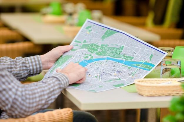 Blanke jonge europese man met stadsplan in openlucht café. portret van aantrekkelijke jonge toerist op lunchtijd