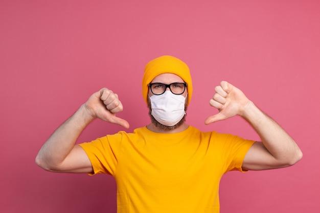 Blanke jonge man in glazen met medisch masker voor eenmalig gebruik om infectie, luchtwegaandoeningen zoals griep te voorkomen