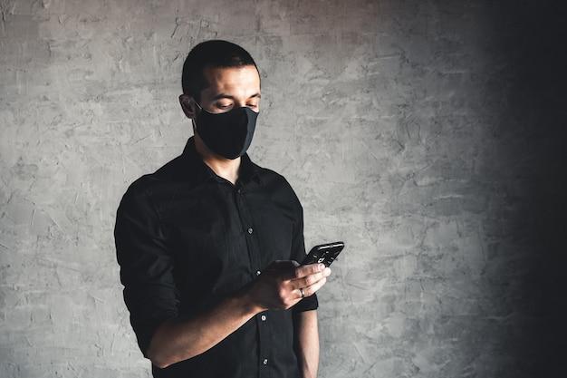 Blanke jonge man in wegwerp gezichtsmasker. bescherming tegen virussen en infectie. hij belt op, mogelijk een ambulance voor hulp. kopieer ruimte.