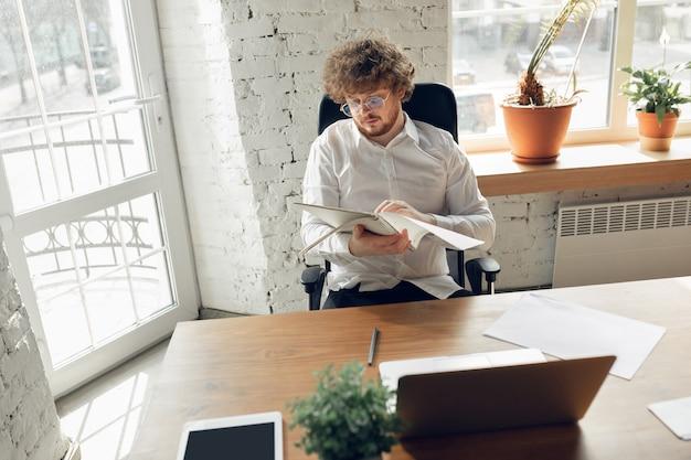 Blanke jonge man in zakelijke kleding werkzaam in kantoorbaan online studeren