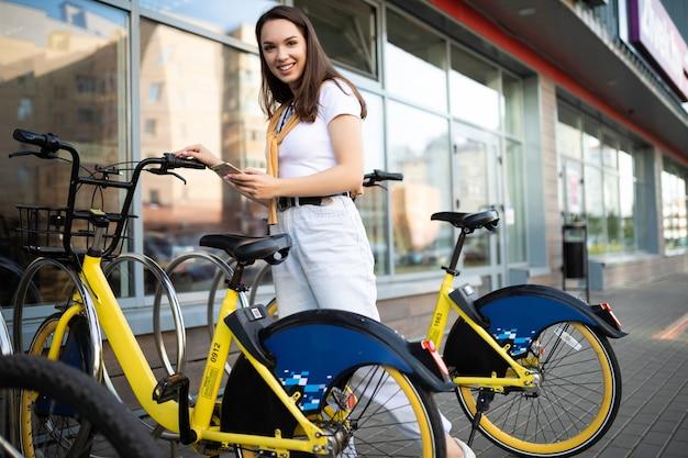 Blanke jonge vrouw betaalt fietshuur in app