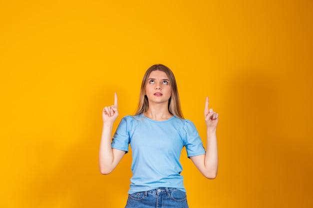 Blanke jonge vrouw die omhoog wijst met vrije ruimte voor tekst.
