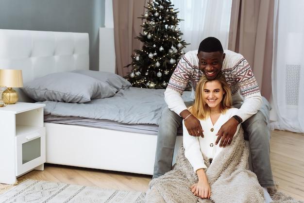 Blanke jonge vrouw en zwarte man knuffelen elkaar op het bed thuis tegen de achtergrond van een kerstboom.
