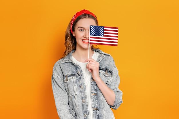 Blanke jonge vrouw in spijkerjasje bedekt de helft van haar gezicht met een kleine amerikaanse vlag en glimlacht geïsoleerd over oranje muur