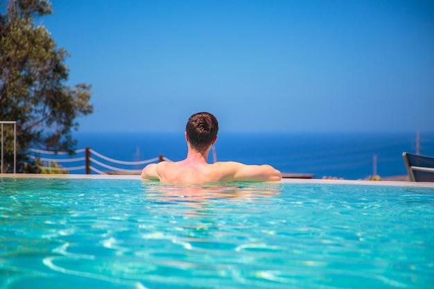 Blanke jongeman in het overloopzwembad kijkt naar het uitzicht op de oceaan, ontspant en geniet van zijn leven