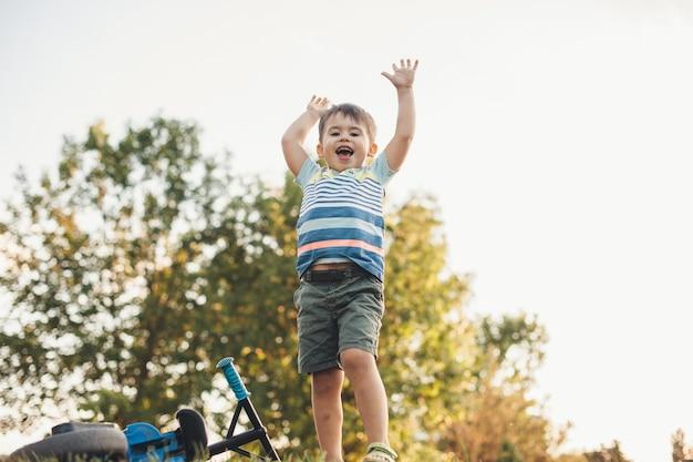 Blanke jongen buiten spelen met de fiets hand in hand omhoog en glimlachen naar de camera
