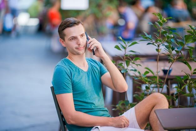 Blanke jongen houdt mobiel buitenshuis op straat. man met behulp van mobiele smartphone.