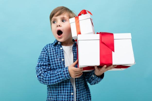 Blanke jongen houdt veel witte dozen met geschenken en verheugt zich, portret geïsoleerd op blauw
