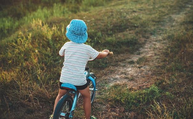 Blanke jongen in een blauwe hoed met de fiets in een veld