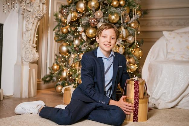 Blanke jongen in pak zit in de buurt van kerstcadeau schattige tiener naast cadeau voor kerst wacht tot...