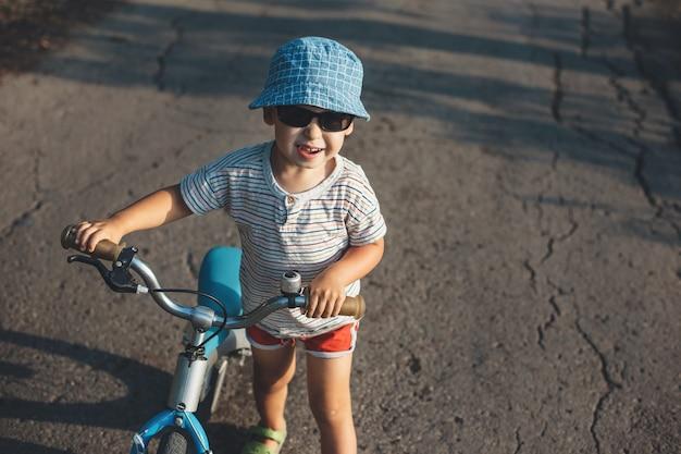 Blanke jongen met blauwe hoed en zonnebril glimlachend in de camera terwijl hij de fiets op de weg houdt