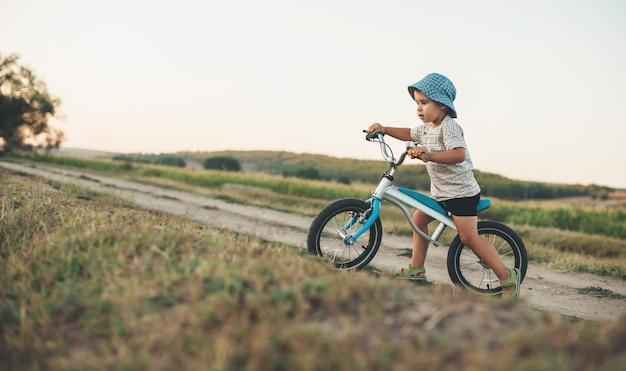 Blanke jongen met blauwe hoed fietsen