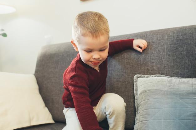 Blanke jongen met blond haar spelen op de bank met speelgoed poseren in de buurt van kussens