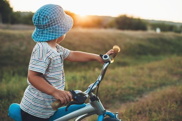 Blanke jongen met een hoed fietsen op het platteland