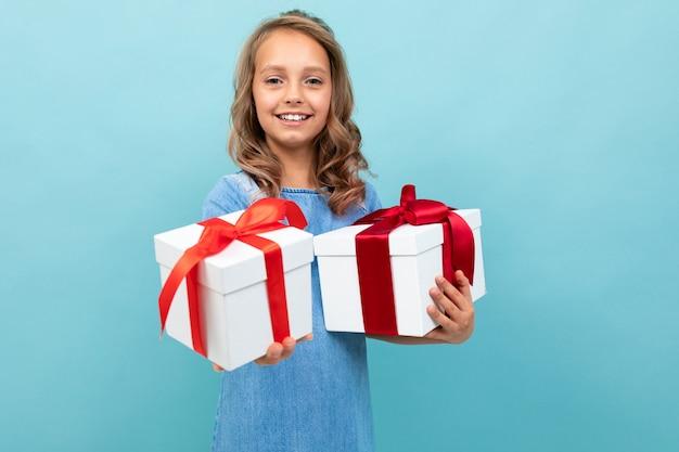 Blanke kind houdt veel witte dozen met geschenken en verheugt zich, portret geïsoleerd op blauw