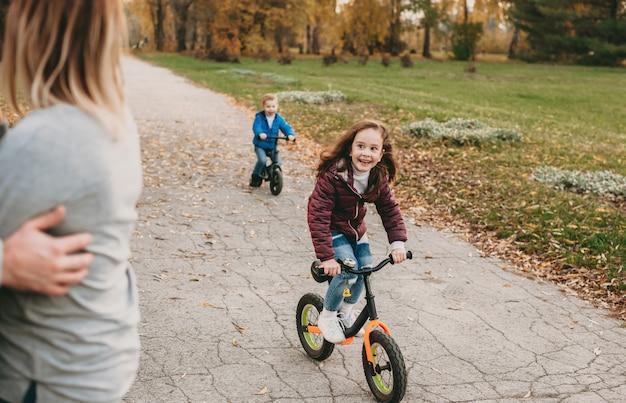 Blanke kinderen fietsen en glimlachen gelukkig naar hun ouders tijdens een wandeling samen in het park