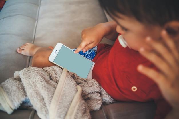Blanke kleine jongen zit in bed en houdt een telefoon vast terwijl hij naar het scherm kijkt dat bedekt is met een sprei