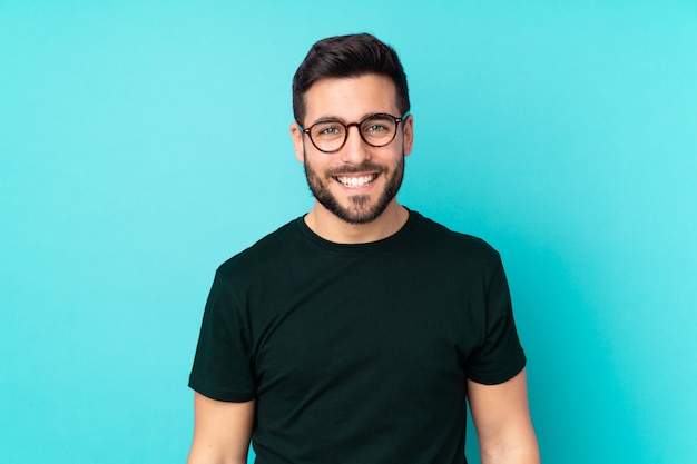 Blanke knappe man geïsoleerd op blauwe muur met een bril en gelukkig