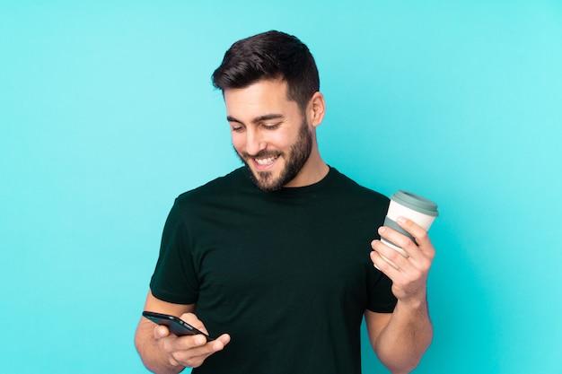 Blanke knappe man geïsoleerd op blauwe muur met koffie om mee te nemen en een mobiel