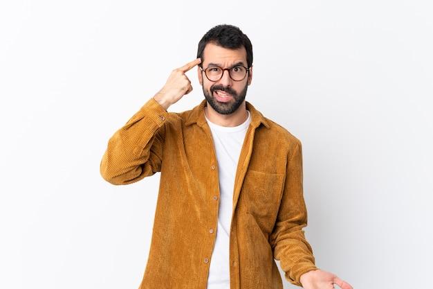 Blanke knappe man met baard draagt een corduroy jas over wit waardoor het gebaar van waanzin vinger op het hoofd