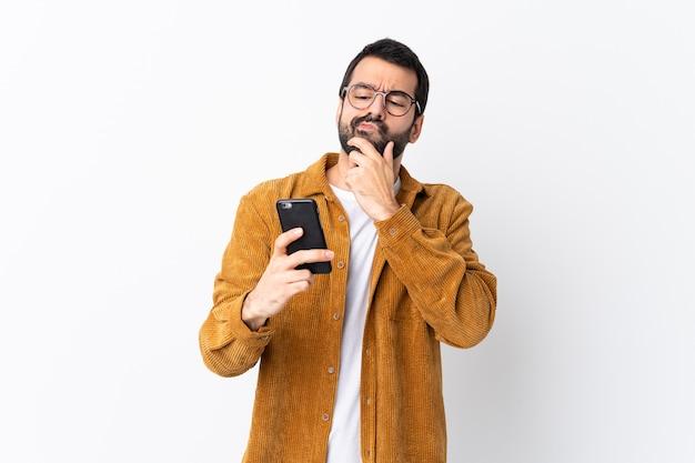 Blanke knappe man met baard draagt een corduroy jasje over wit denken en een bericht verzenden