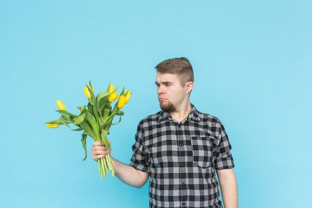 Blanke knappe man met bos gele tulpen