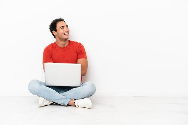 Blanke knappe man met een laptop die blij en glimlachend op de grond zit