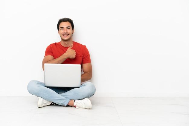 Blanke knappe man met een laptop die op de grond zit en een duim omhoog gebaar geeft