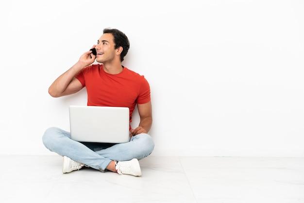 Blanke knappe man met een laptop die op de grond zit en een gesprek voert met de mobiele telefoon
