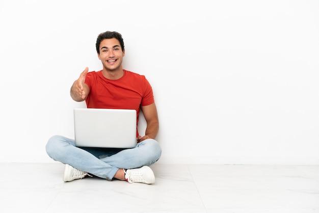 Blanke knappe man met een laptop die op de grond zit en handen schudt voor het sluiten van een goede deal